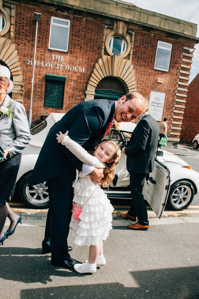 Groom getting hugs from the flowergirl outside St Aidan's RC Church in Ashington