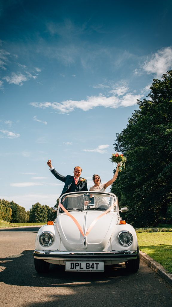 Bride & Groom cheering on arrival in their White VW Beetle at Beamish Park Hotel