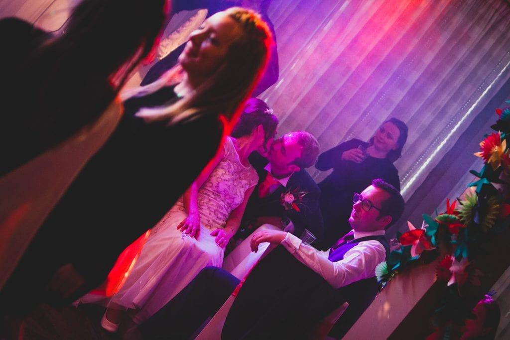 Bride & Groom having a sneaky kiss behind Irish Dancers at Beamish Park Hotel