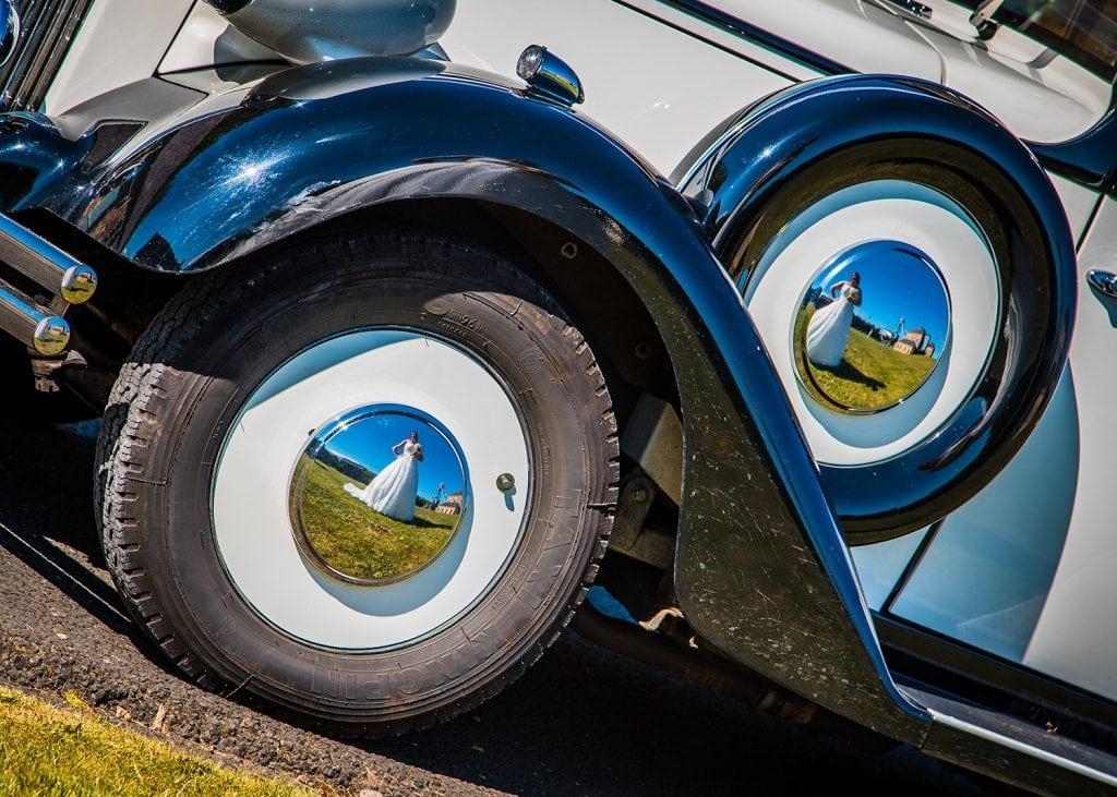 Bride reflected in Rolls-Royces wheel caps