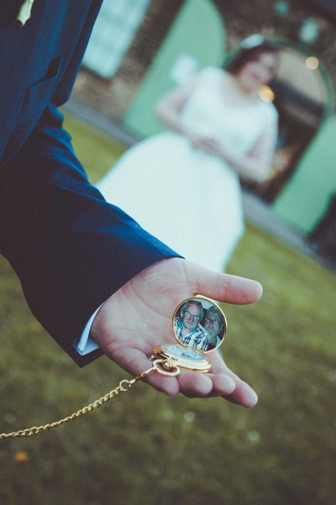 Groom holding his pocket watch