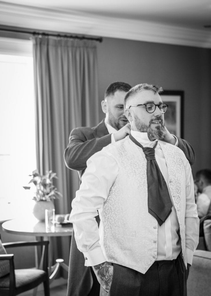 Usher helping the groom get ready