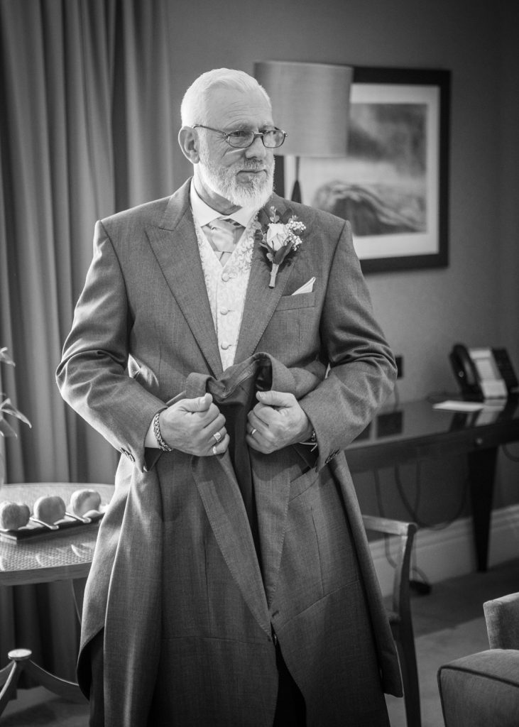 Grooms dad hold his suit jacket
