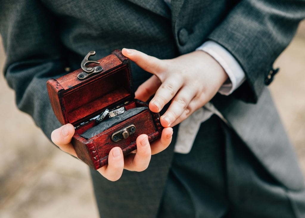 Ring bearer holding wedding rings in a small wooden chest