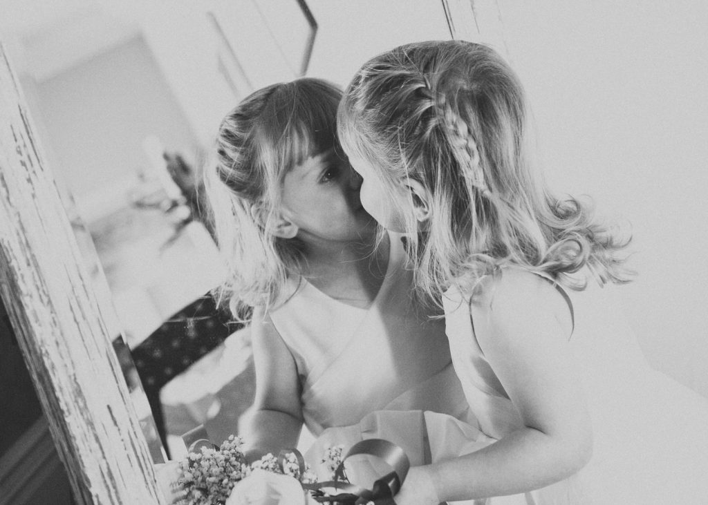 Flower girl kissing herself in the mirror