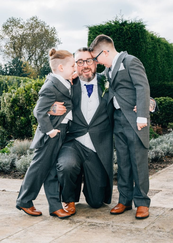 Groom hugging his two sons