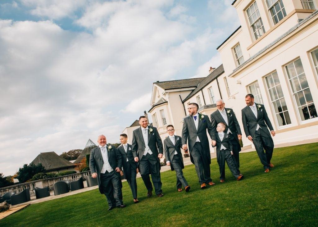 Groomsmen walking through Seaham Hall Gardens