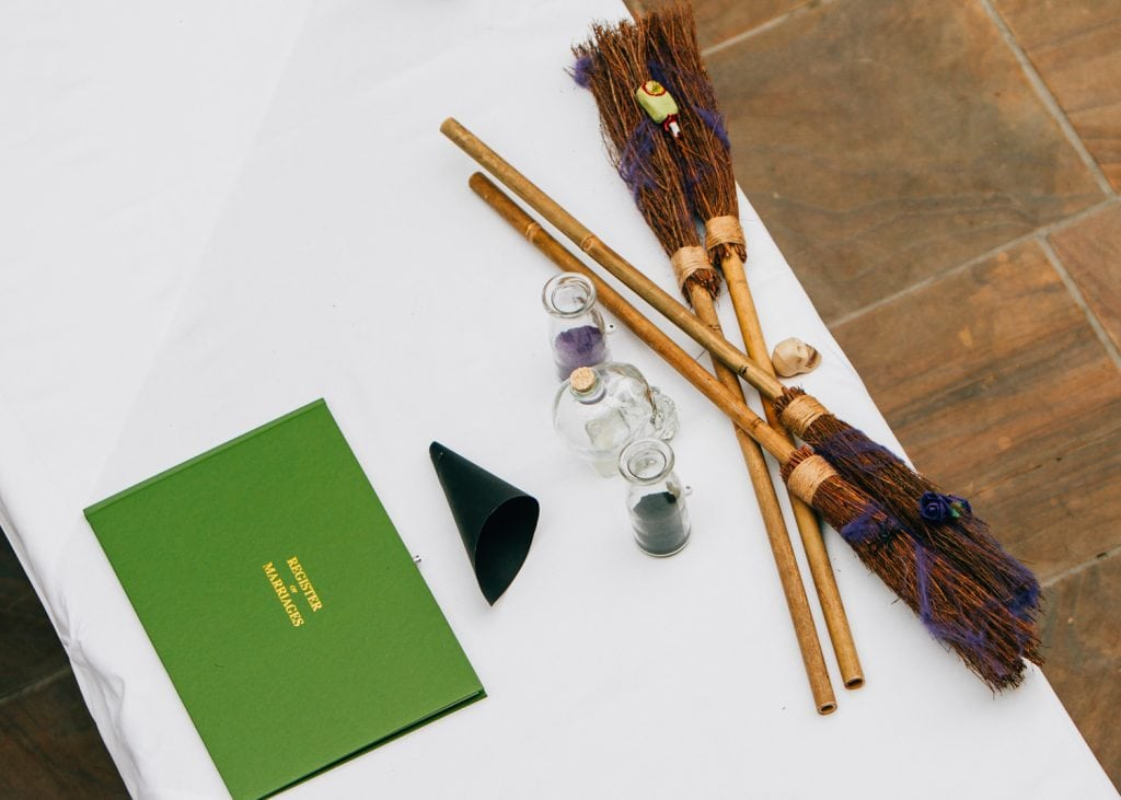 Registry book next to witches brooms on the service table