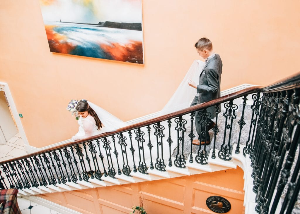 Bride walking down Seaham Hall stairs
