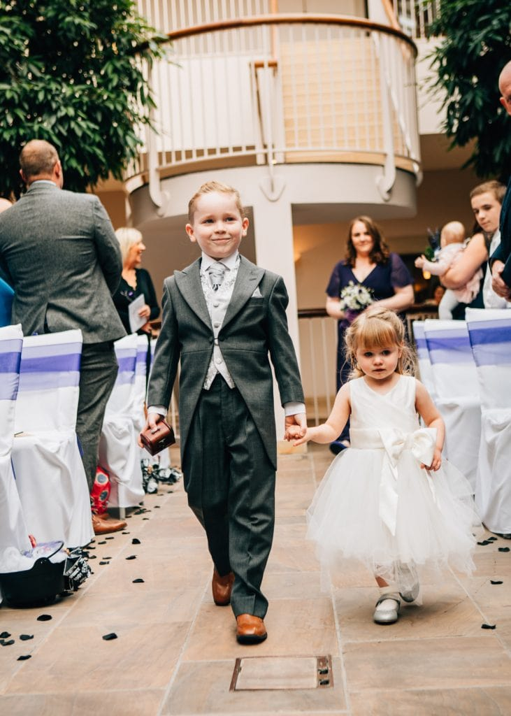 Page boy hand in hand with flower girl