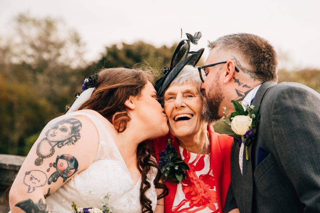 Bride & Groom kissing grandma