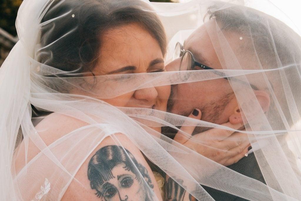 Groom kissing the bride under her veil