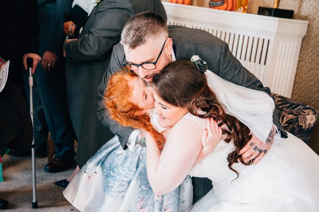 Bride & Groom hugging young guest