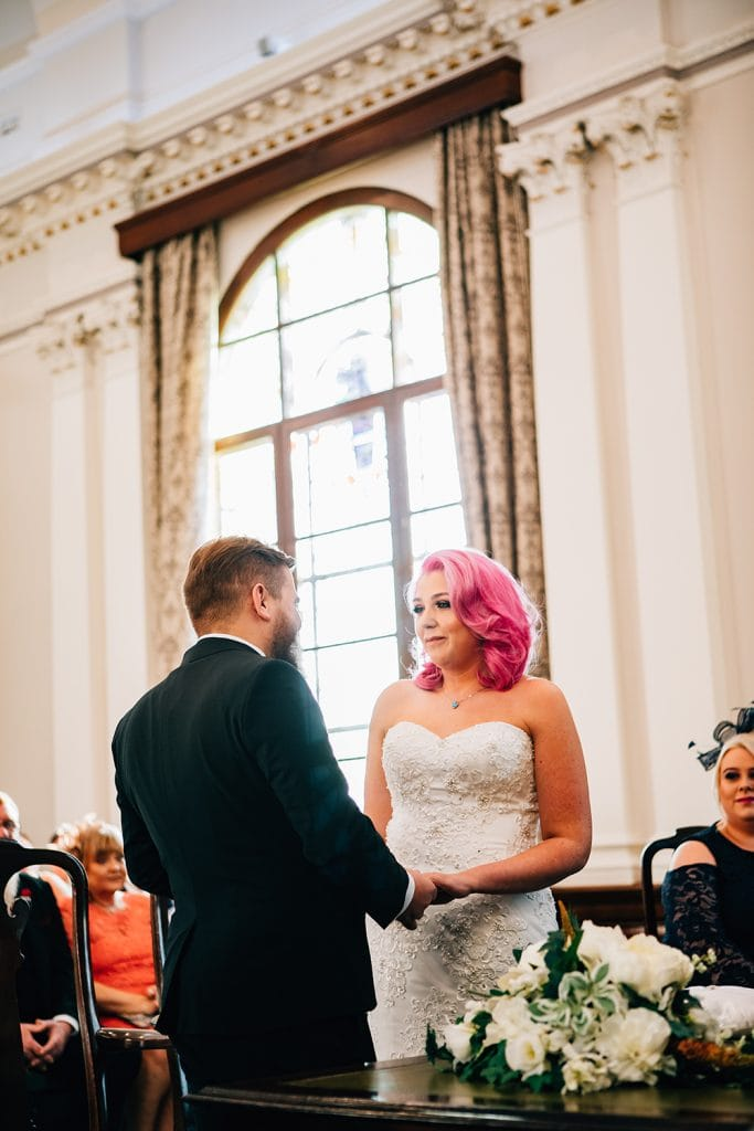 Groom holding Brides hands during wedding service