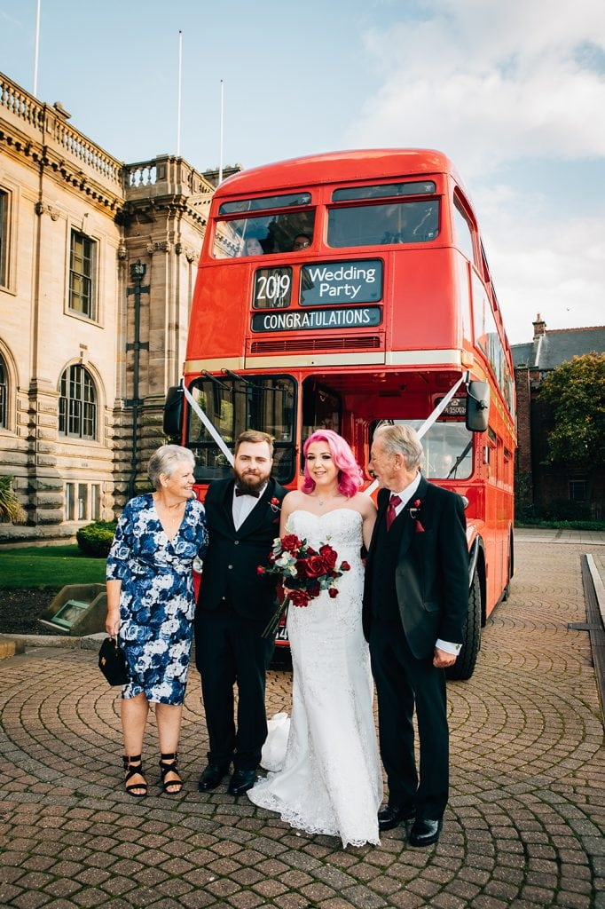 Grandparent with the bride & groom with there red london bus