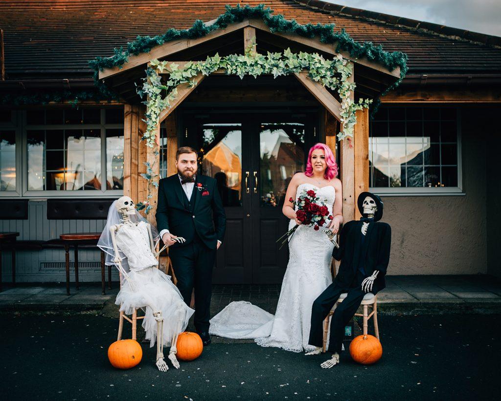 Bride & Groom with Halloween Skeletons outside the Greyhound Inn