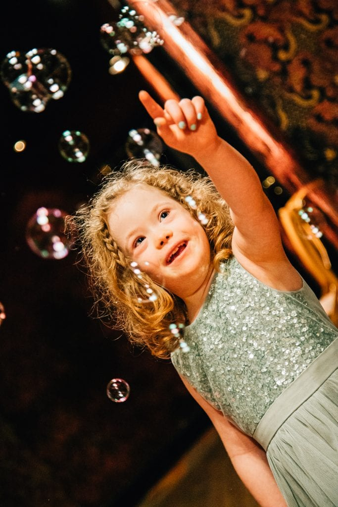 Bridesmaid playing with bubbles