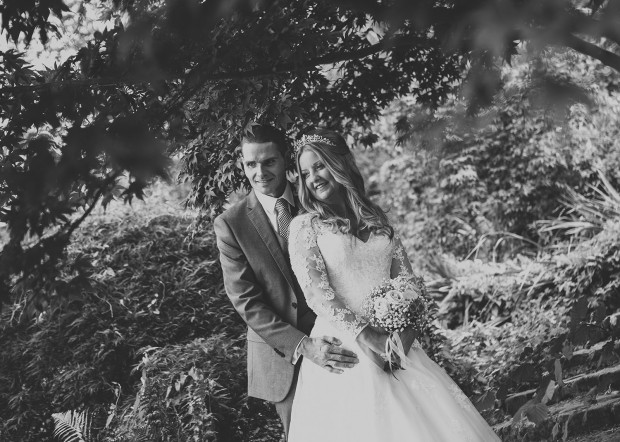 The bride & groom under trees at Carlisle Park in Morpeth, Northumberland